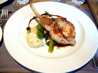 Côtelette de porc suisse rassise sur l'os, frites à la marjolaine, légumes de saison et beurre au vin rouge