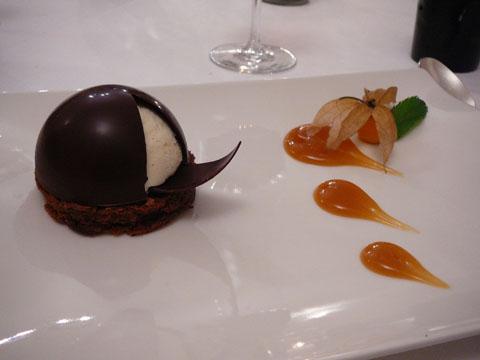 Sur un biscuit au chocolat mi-cuit, soufflé glacé au Grand Marnier et dôme chocolat Valrhona