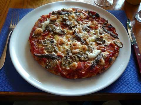 Pizza Vesuvio : tomates, mozarelle, calamars, jambon, champignon, anchois, crevettes, épices