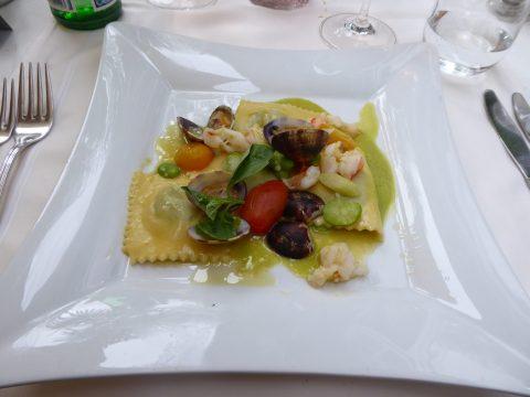 Raviolis d'asperges en sauce fine aux haricots blancs, asperges vertes, tomates dattes mélangées, palourdes et crevettes, servis sur une crème de petits pois